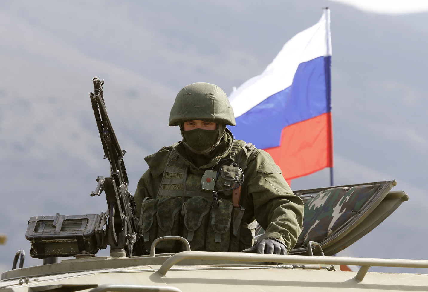 An armed man, believed to be Russian serviceman, stands guard outside a Ukrainian military base in Perevalnoye